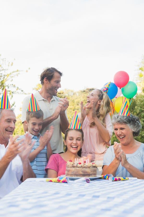 Vrolijke uitgebreide familie die voor meisjesverjaardag slaan royalty-vrije stock fotografie