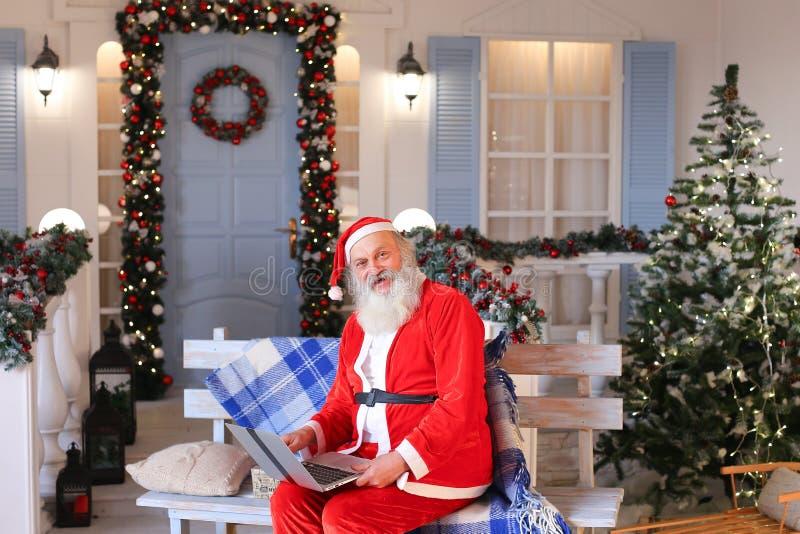Vrolijke Vader Christmas dat met video door laptop spreekt stock afbeeldingen