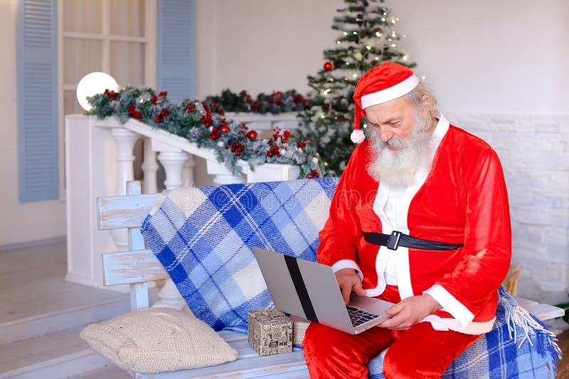 Vrolijke Vader Christmas dat met video door laptop spreekt stock foto