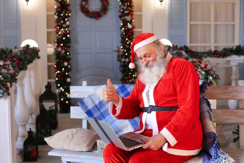 Vrolijke Vader Christmas dat met video door laptop spreekt stock afbeelding