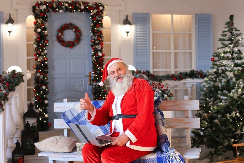 Vrolijke Vader Christmas dat met video door laptop spreekt royalty-vrije stock foto's
