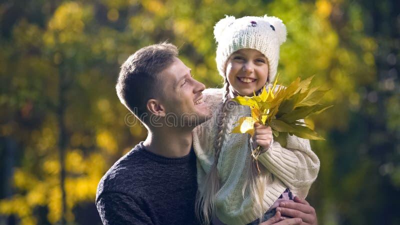 Vrolijke vader die leuke dochter houden, die in de herfstpark wandelen, vaderschap stock fotografie