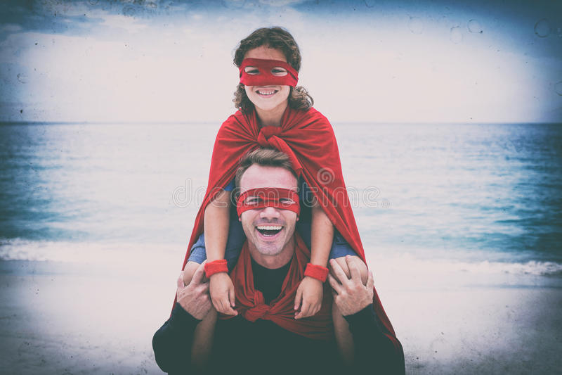 Vrolijke vader en zoon die in superherokostuum bij strand genieten van stock foto's