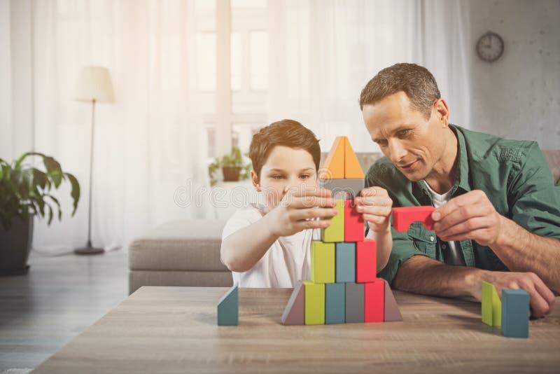 Vrolijke vader en zoon die toren van blokken thuis construeren royalty-vrije stock foto's