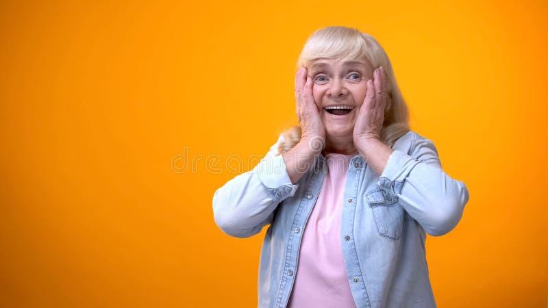 Vrolijke verraste bejaarde dame tevreden met nieuws, kortingen en vakantieverkoop stock afbeeldingen