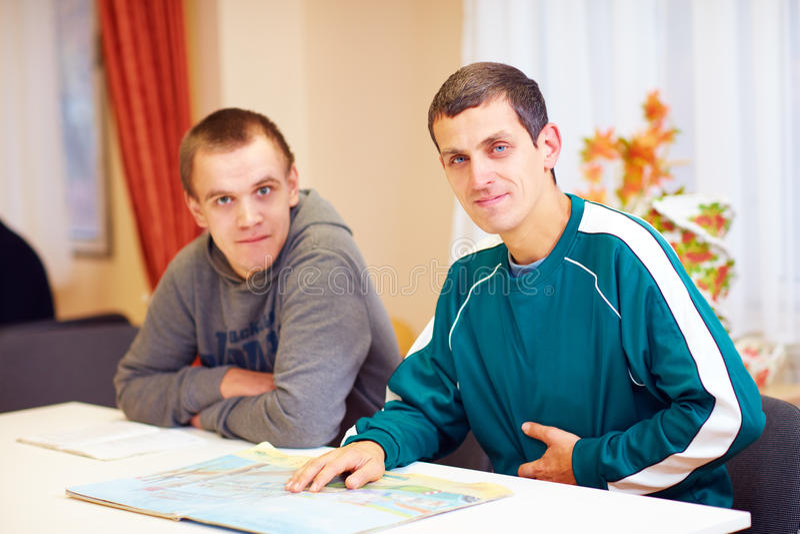 Vrolijke volwassen mensen met onbekwaamheidszitting bij het bureau in revalidatiecentrum royalty-vrije stock foto's