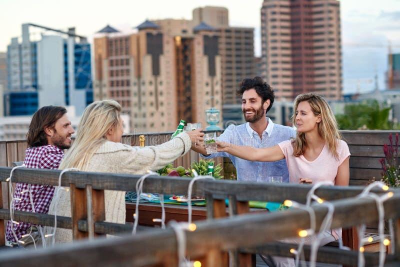 Vrolijke vrienden die cocktails en bieren drinken stock afbeelding
