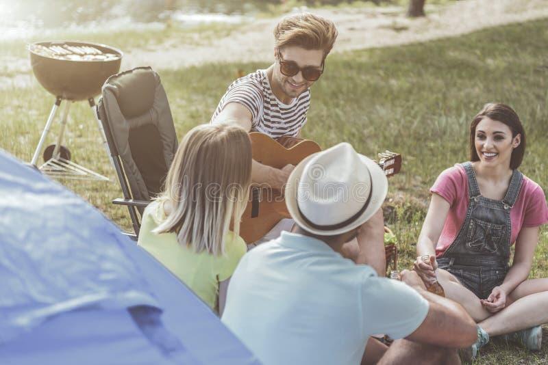 Vrolijke vrienden die picknick met een lied organiseren stock foto