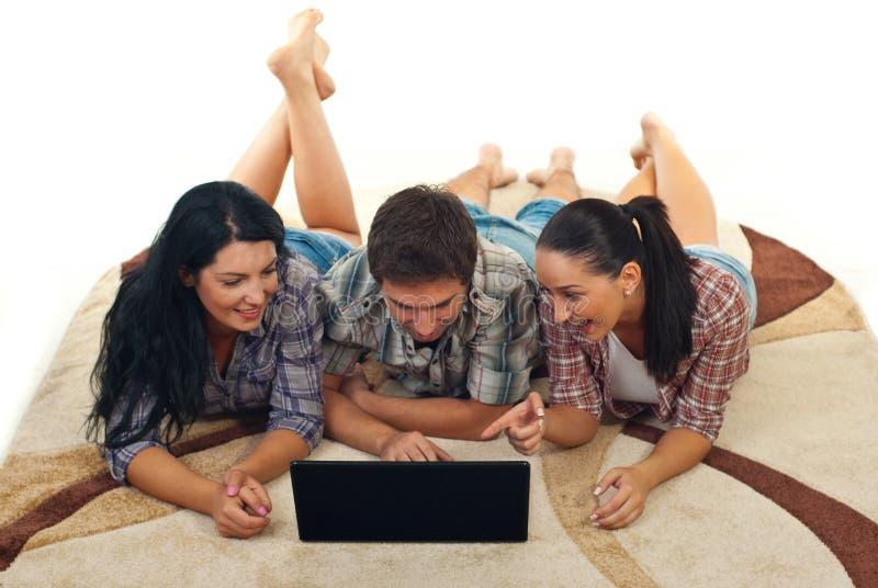 Vrolijke vrienden op tapijt dat laptop met behulp van stock afbeelding