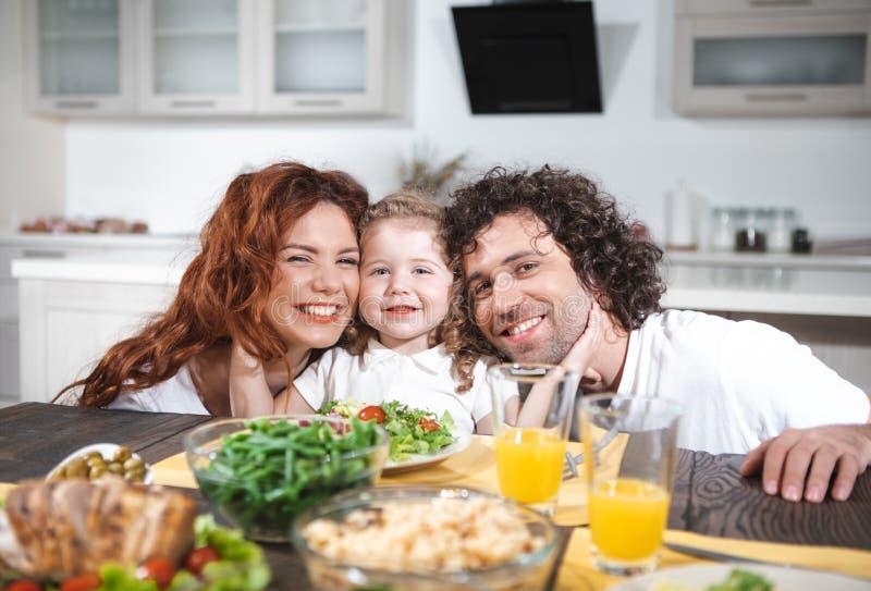 Vrolijke vriendschappelijke familie die in keuken samen eten stock afbeelding