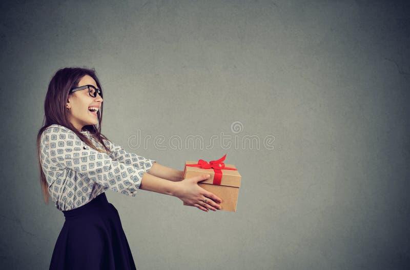 Vrolijke vrouw die aanwezige Kerstmis geven royalty-vrije stock afbeelding