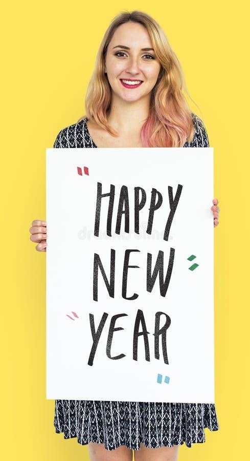 Vrolijke vrouw die een gelukkige nieuwe jaaraffiche houden royalty-vrije stock afbeeldingen