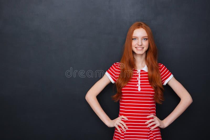 Vrolijke vrouw die en zich over bordachtergrond bevinden glimlachen stock foto