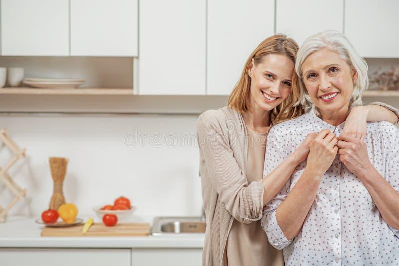 Vrolijke vrouw die haar hogere ouder in keuken omhelzen stock foto