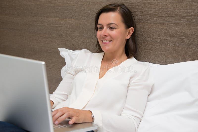 Vrolijke vrouw die haar laptop in de slaapkamer met behulp van stock afbeeldingen