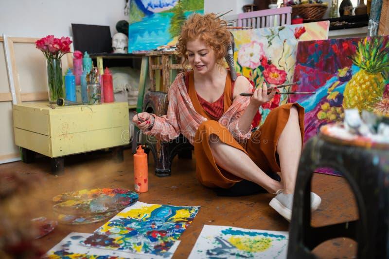 Vrolijke vrouw die het gelukkige schilderen op vloer voelen stock fotografie