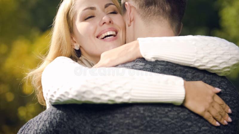 Vrolijke vrouw die mens omhelzen, die ja voor voorstel, gelukkige ogenblikken, liefde de zeggen stock foto