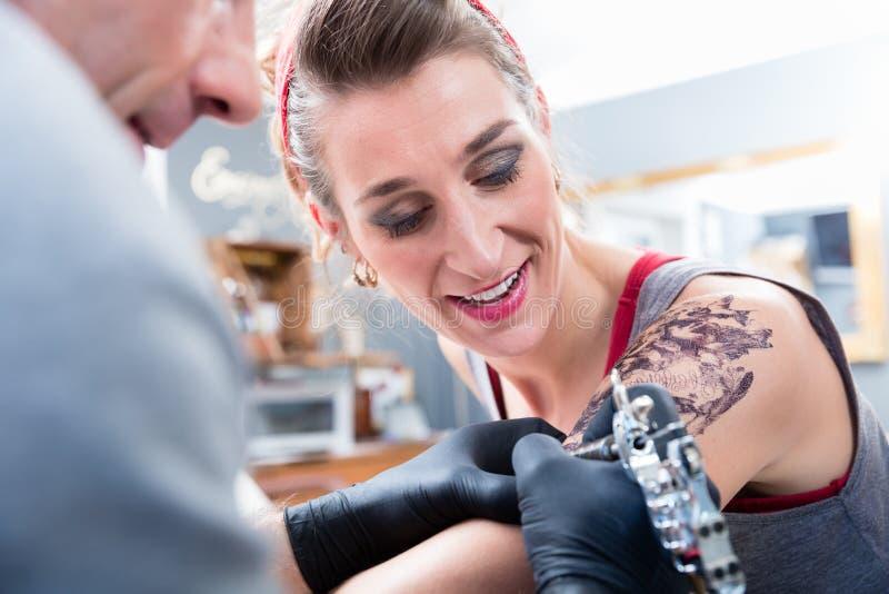 Vrolijke vrouw die met vertrouwen in een moderne tatoegeringsstudio glimlachen royalty-vrije stock foto
