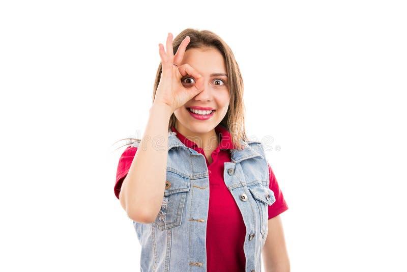 Vrolijke vrouw die O.K. teken met glimlach tonen stock afbeelding