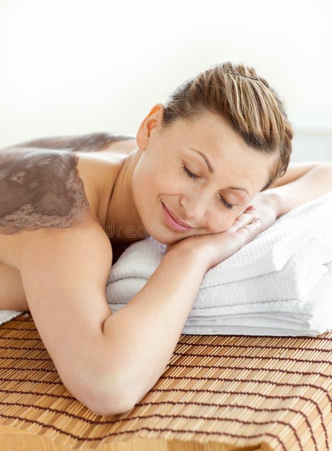 Vrolijke vrouw die op een massagelijst ligt met modder stock afbeeldingen