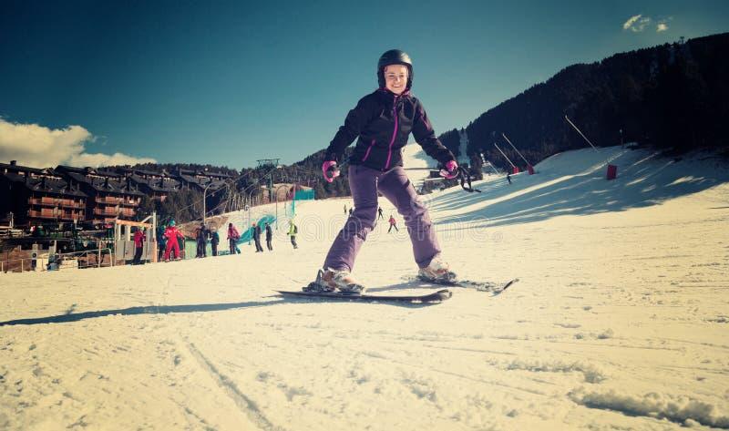 Vrolijke vrouw die op sneeuwberg ski?en royalty-vrije stock afbeelding