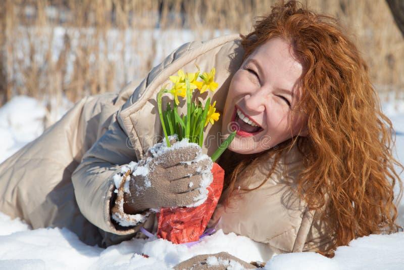 Vrolijke vrouw die op sneeuwoppervlakte liggen met gele in hand narcissuses stock foto