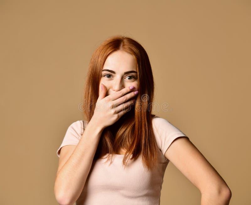 Vrolijke vrouw die pret hebben die in het lachen houdende hand op mond barsten stock fotografie