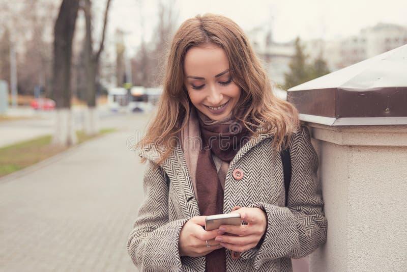 Vrolijke vrouw die telefoon in openlucht met behulp van royalty-vrije stock afbeeldingen
