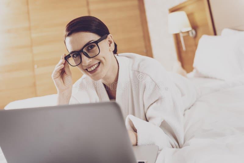 Vrolijke vrouw het besteden tijd met laptop stock afbeelding