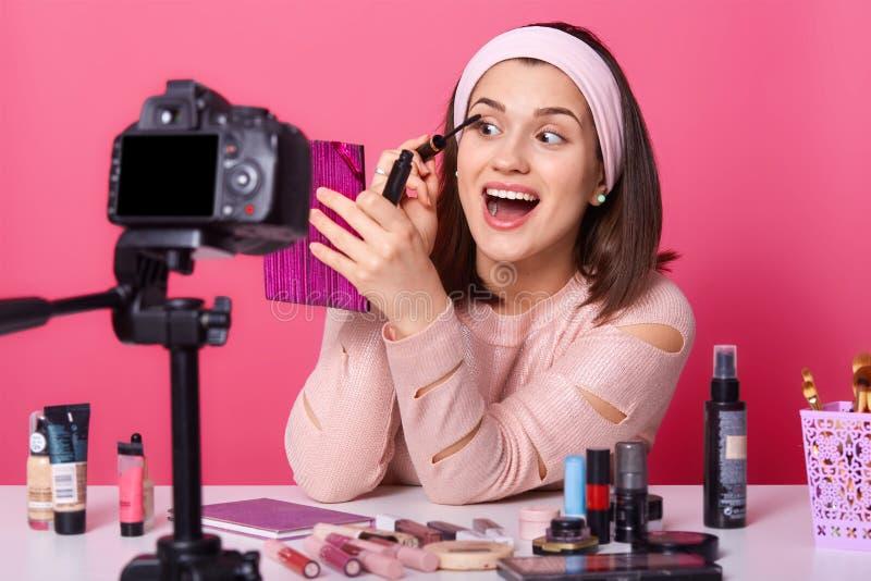 Vrolijke vrouw met brede geopende mond en ogen die leerprogramma voor haar abonnees maken, die roze spiegel houden, toepassend ma royalty-vrije stock foto