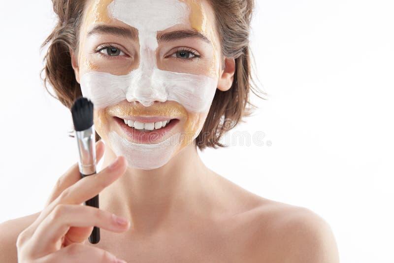 Vrolijke vrouw met gezichtsmasker en borstel stock afbeeldingen