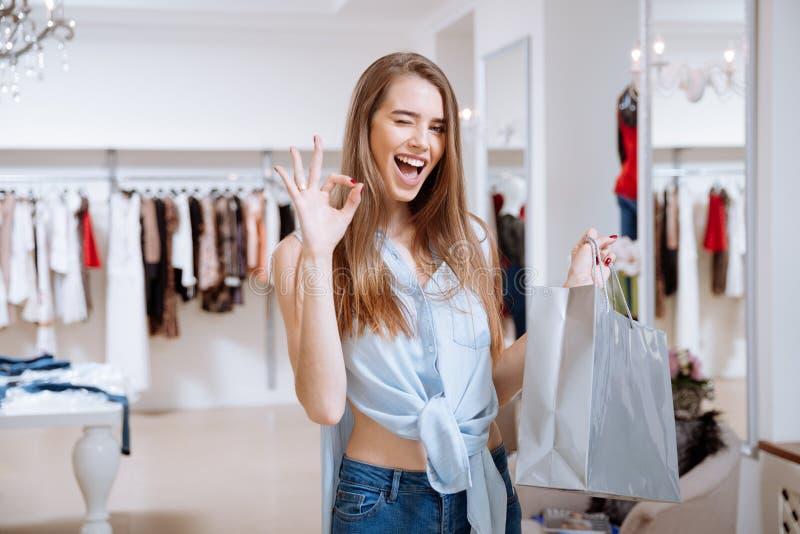Vrolijke vrouw met het winkelen zak die o.k. in kledingsopslag tonen stock afbeelding