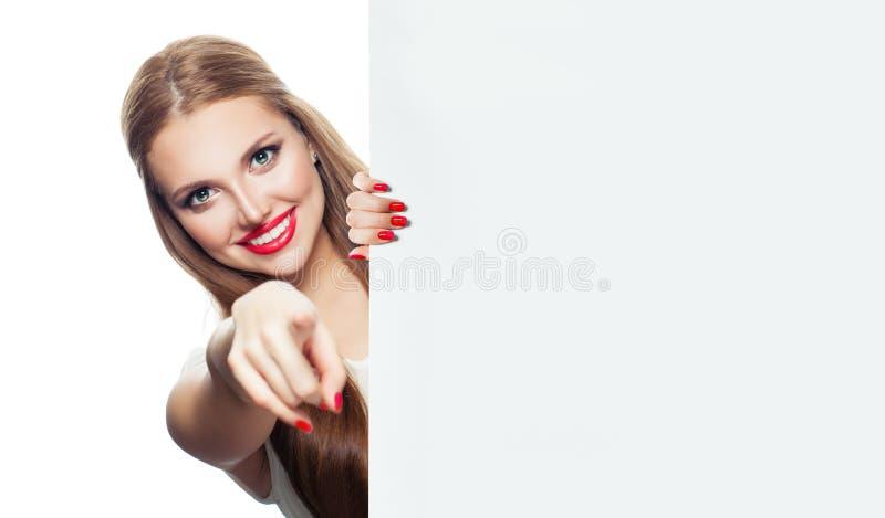 Vrolijke vrouw met wit leeg en karton die geïsoleerd op witte achtergrond glimlachen richten stock afbeelding