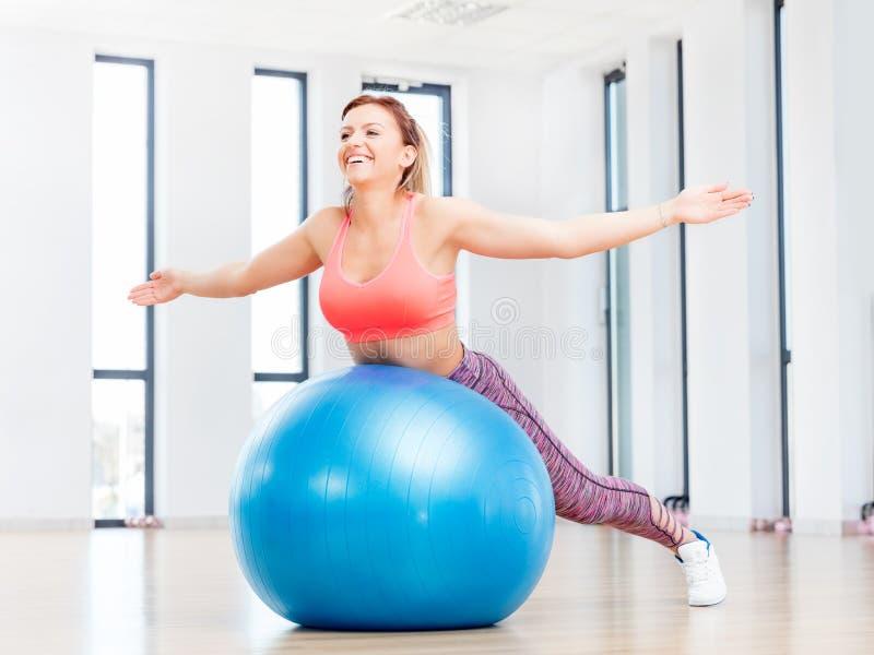 Vrolijke vrouw opleiding met fitball bij geschiktheidsclub stock afbeelding