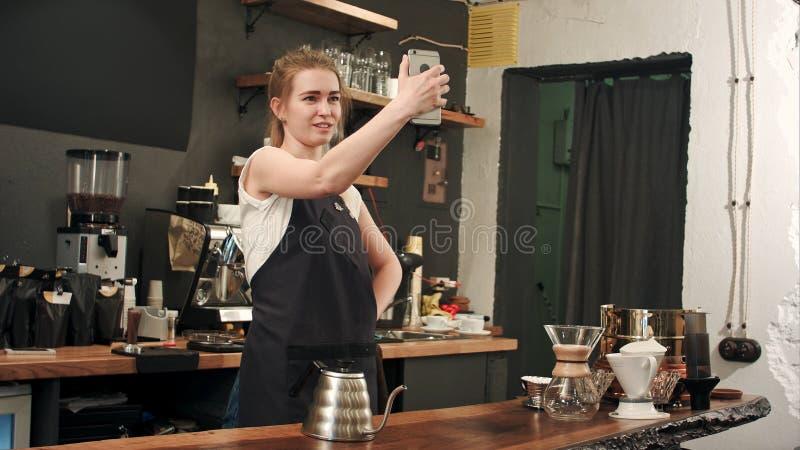 Vrolijke vrouwelijke barista gebruikend smartphone om selfie in koffiewinkel te nemen royalty-vrije stock afbeeldingen