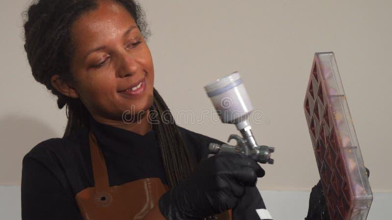 Vrolijke vrouwelijke chef-kok die luchtpenseel met behulp van die chocoladevorm verfraaien royalty-vrije stock afbeelding