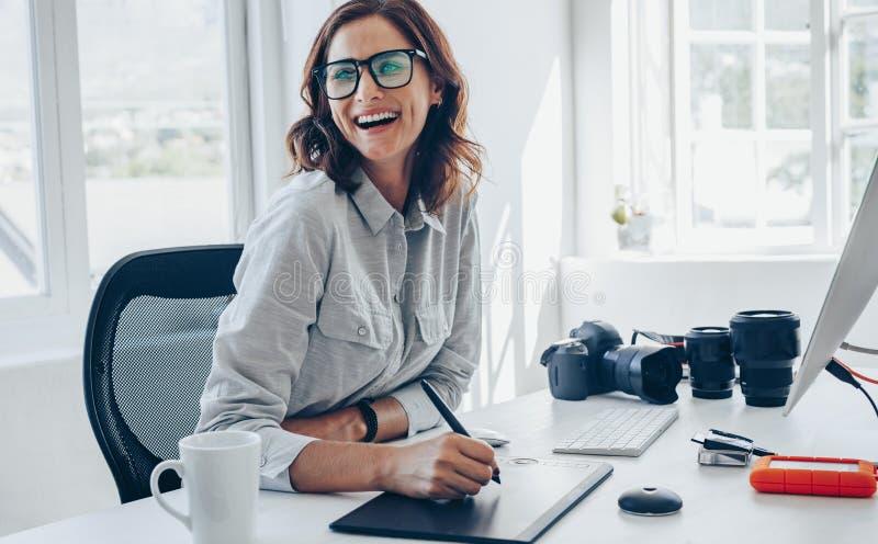 Vrolijke vrouwelijke fotograaf bij haar bureau stock afbeeldingen