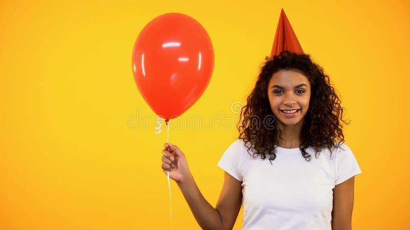 Vrolijke vrouwelijke rode ballon houden en tiener die, verjaardagsviering, pret glimlachen stock afbeeldingen