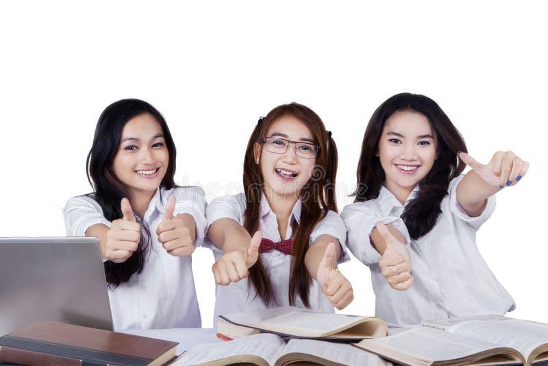 Vrolijke vrouwelijke studenten met omhoog duimen stock afbeelding