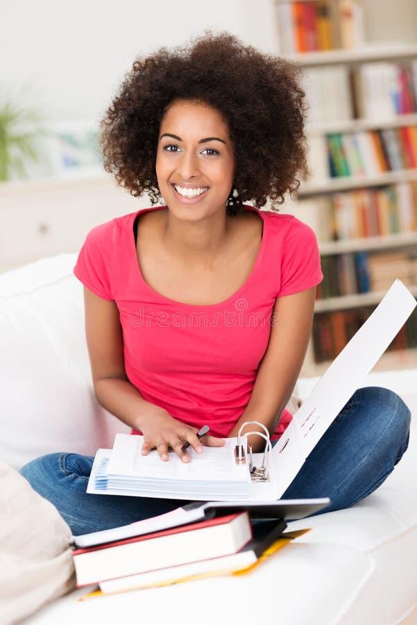 Vrolijke vrouwelijke studentenzitting op de bank royalty-vrije stock fotografie