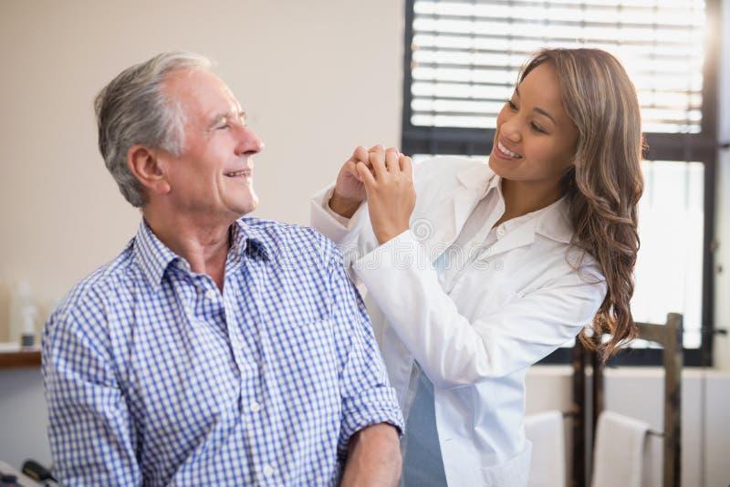 Vrolijke vrouwelijke therapeut en hogere mannelijke patiënt die elkaar bekijken royalty-vrije stock foto's