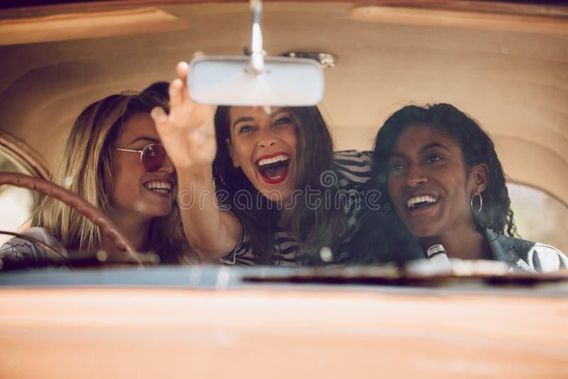 Vrolijke vrouwelijke vrienden die op een wegreis gaan royalty-vrije stock foto