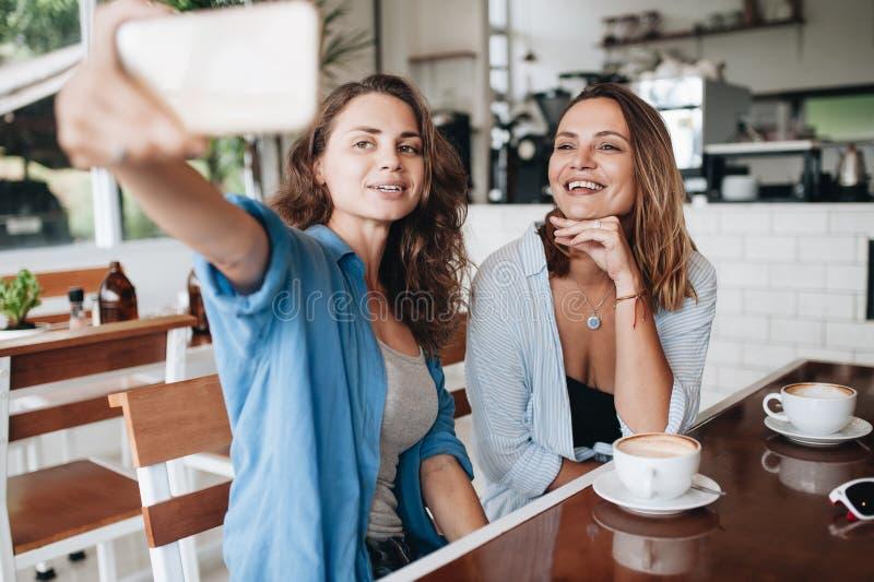 Vrolijke vrouwelijke vrienden die selfie beeld in koffie nemen Twee mooie jonge vrouwen die en aan de camera glimlachen kijken stock fotografie