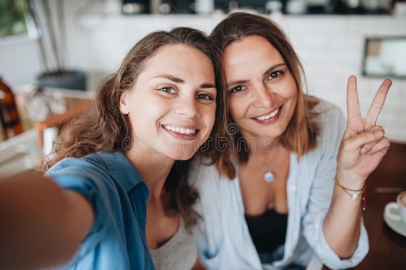 Vrolijke vrouwelijke vrienden die selfie beeld in koffie nemen Twee mooie jonge vrouwen die en aan de camera glimlachen kijken royalty-vrije stock foto