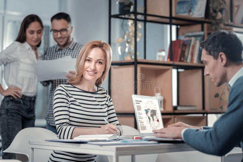 Vrolijke vrouwelijke werknemer die in haar notitieboekje schrijven stock afbeeldingen
