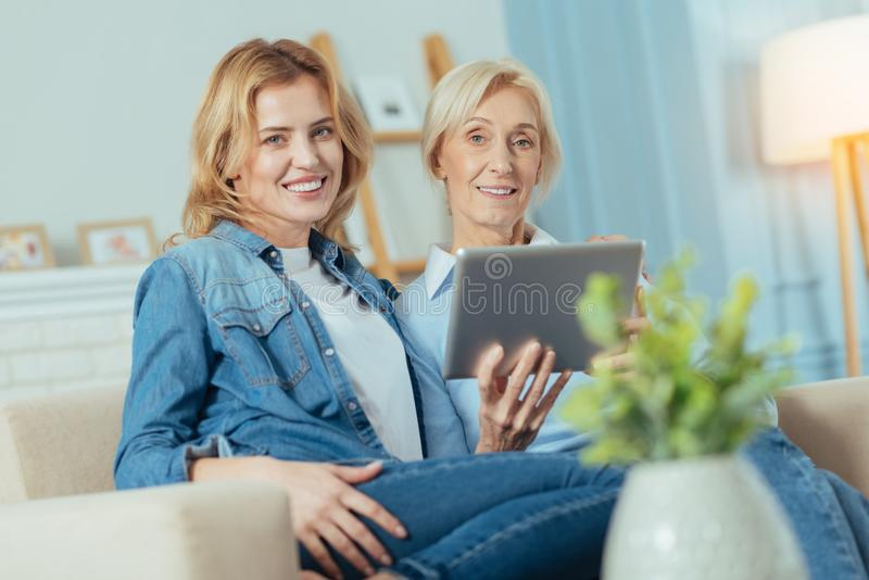 Vrolijke vrouwen die op een bank zitten en een moderne tablet houden royalty-vrije stock fotografie