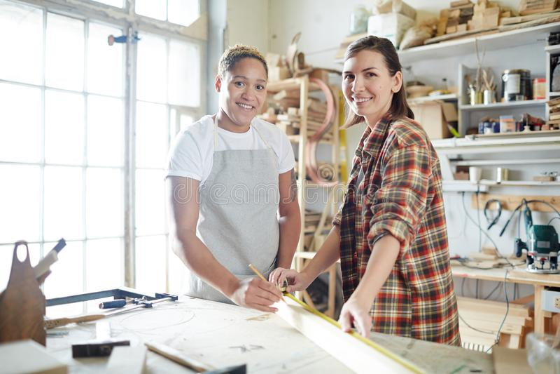 Vrolijke vrouwen die in timmermansworkshop werken royalty-vrije stock foto's
