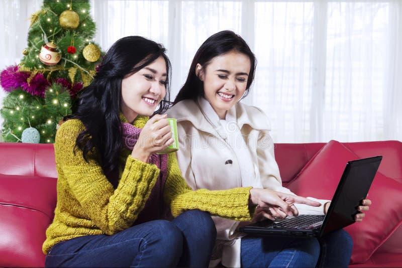 Vrolijke vrouwen met laptop in Kerstmistijd stock afbeelding