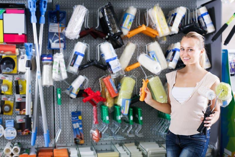 Vrolijke vrouwenklant het kopen het schilderen rol in huishoudenstor stock foto