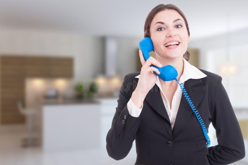 Vrolijke vrouwenmakelaar in onroerend goed die een gesprek op telefoon hebben royalty-vrije stock afbeelding